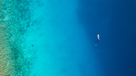 Aerial view of young man riding paddleboard. Paddleboarding is the modern way of transportation and water activity sport. Stock Photo