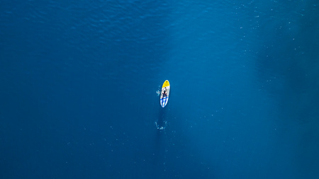 Aerial view of young man riding paddleboard. Paddleboarding is the modern way of transportation and water activity sport.