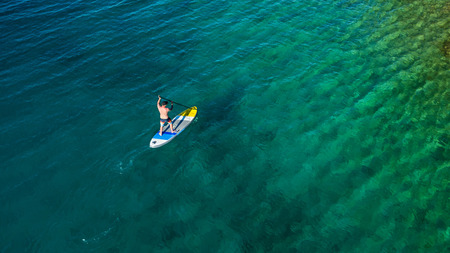 Aerial view of young man riding paddleboard. Paddleboarding is the modern way of transportation and water activity sport. 版權商用圖片 - 105126053