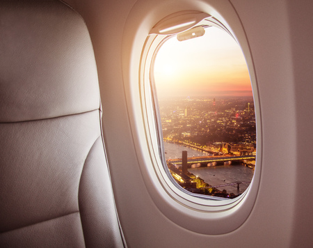 Airplane interior with window view of London city, Europe. Concept of travel and air transportation