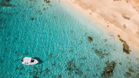 Small motor boat anchoring at sandy beach, aerial view. Active life style, water transportation and marine sport. Stock fotó