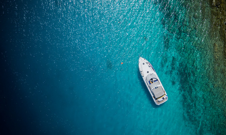 Luxury small yacht anchoring in shallow water, aerial view. Active life style, water transportation and marine sport. Reklamní fotografie