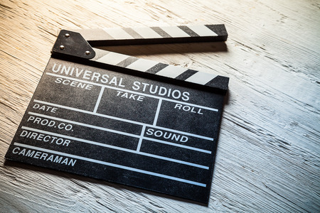 Vintage film clapper on wooden desk. Filmmakers equipment background Foto de archivo