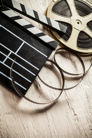 Vintage film claper with film reel placed on wood. Filmammakers equipment background Stock Photo