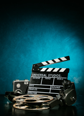 Vintage film claper with film reel and camera. filmmakers equipment background Stock Photo