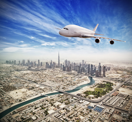 Huge commercial jetliner flying above Dubai city, UAE. Modern and fastest mode of transportation, symbol of luxury and business traveling.