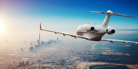 Luxury private jetliner flying above Dubai city, UAE. Modern and fastest mode of transportation, symbol of luxury and business traveling.