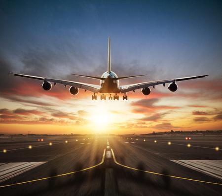 Reusachtige twee verdiepingen tellende commerciële jetliner die de landingsbaan inneemt. Modern en snelste vervoermiddel. Dramatische zonsonderganghemel op achtergrond