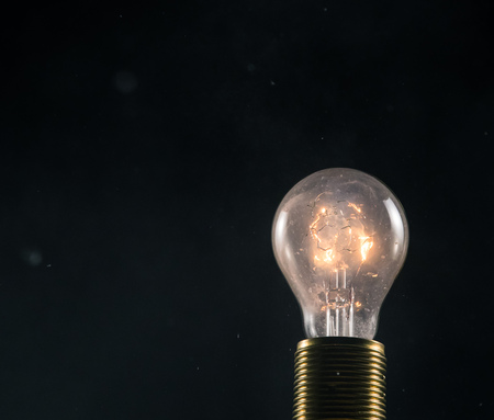 Burning old light bulb on black backround. Concept of new idea and brain storming. Archivio Fotografico