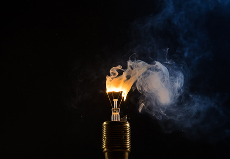 Burning old light bulb on black backround. Concept of new idea and brain storming. Reklamní fotografie