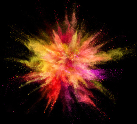 Explosion of coloured powder isolated on black background. Abstract colored background