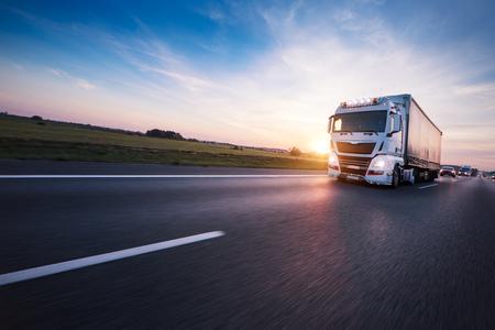 Camion europeo caricato sull'autostrada nella splendida luce del tramonto. Sul trasporto stradale e merci. Archivio Fotografico