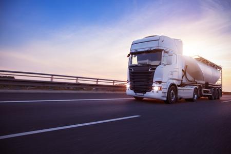 Loaded European truck tank on motorway in beautiful sunset light. On the road transportation and cargo. Standard-Bild