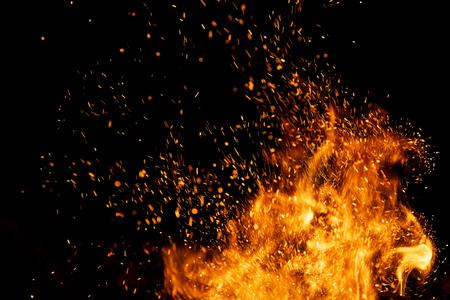 Le feu étincelle des particules avec des flammes isolées sur fond noir. Banque d'images