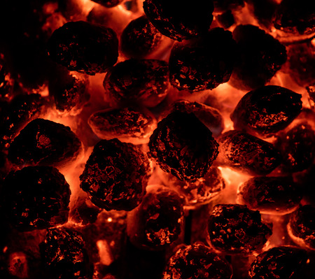 Flaming hot charcoal briquettes in detail.
