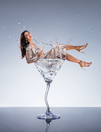 Beautiful young brunette woman in Martini drink. Concept of celebration and drink