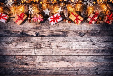 Decorative Christmas rustic background with gift boxes on wooden planks. Celebration and holiday concept. Free space for text.