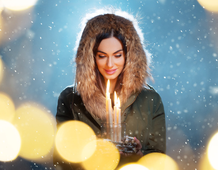Cute brunette young woman holding candles. Concept of winter, Christmas and spirituality. Stock Photo