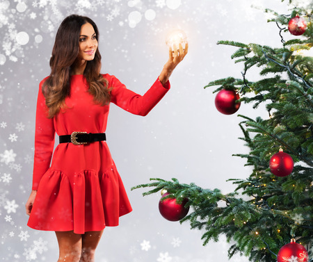 Beautiful young brunette woman in red dress, decorating Christmas tree and holding shining glass ball.