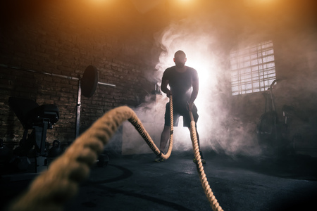 Young man doing hard exercise workout in gym interior with rope waveing. Cinematic mood with dust, dramatic lightning and smoke. Active and healthy lifestyle.