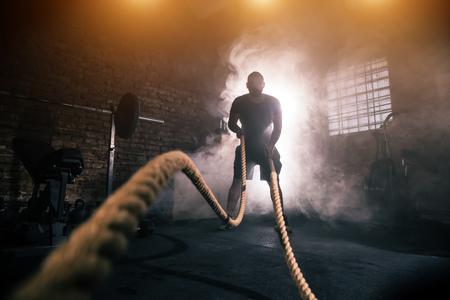 Młody człowiek robi ciężki trening ćwiczeń w wnętrzu siłowni z machaniem liny. Kinowy nastrój z kurzem, dramatycznymi błyskawicami i dymem. Aktywny i zdrowy tryb życia.