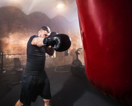 Young man hitting punching bag during training lesson. Dark industrial fitness workout interior with cinematic atmosphere. Active sport and healthy lifestyle.