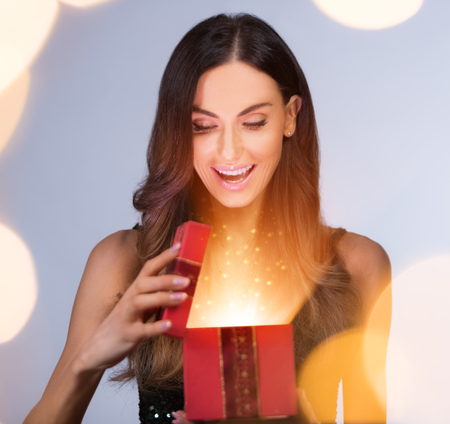 Beautiful brunette young woman holding gift box and making surprise expression. Concept of winter, Christmas and surprise. Imagens