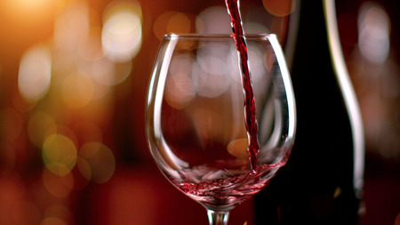Freeze motion of pouring red wine from bottle into goblet. Low depth of focus Stock Photo