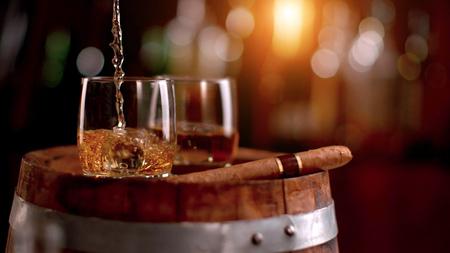 Whisky in Glas gießen. Auf Holzfass gelegt. Geringe Schärfentiefe Standard-Bild