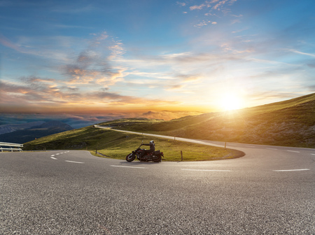Motorcycle driver riding in Alpine road, Austria, Europe. Outdoor photography, mountain landscape. Travel and sport photography. Speed and freedom concept