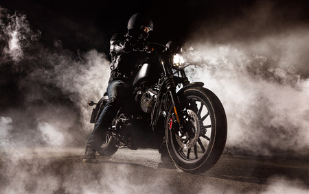 Dark motorcycle driver in fog. Wallpaper design of high power motorbike