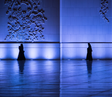 Silhouettes of muslims walking around the mosque wall in Grand Mosque, Abu Dhabi, UAE. Religious motive Stock Photo