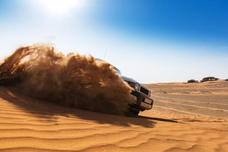 Alla deriva auto fuoristrada 4x4 nel deserto. Congelare il movimento della polvere di sabbia che esplode nell'aria. Azione e attività di svago. Archivio Fotografico