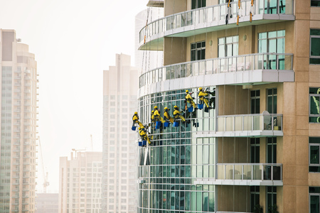 Group of window cleaners washing the glass on skyscraper. Dubai, UAE