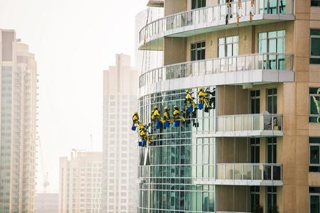 Gruppe von Fensterreinigern, die das Glas auf Wolkenkratzer waschen. Dubai, Vereinigte Arabische Emirate