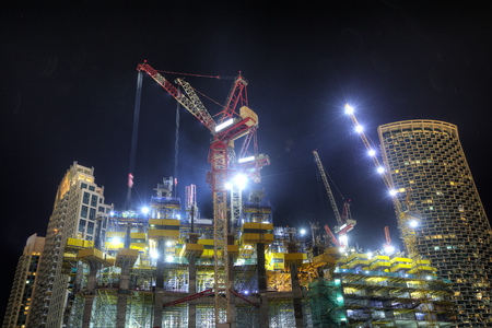 Construction zone with skyscrapers and cranes at night. New and modern architecture building structure in Dubai city, UAE.