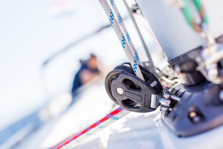 Sailboat winch with rope on yacht deck. Detail, low depth of focus. Leasure activities and extreme sport. Low depth of focus.