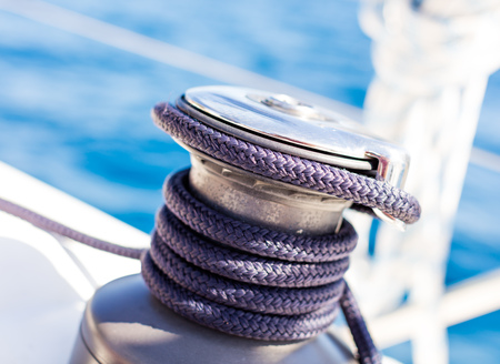 Sailboat winch with rope on yacht deck. Detail, low depth of focus. Leasure activities and extreme sport. Low depth of focus. Stok Fotoğraf - 117028648