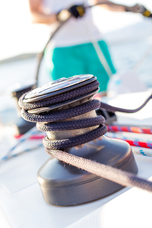 Sailboat winch with rope on yacht deck. Detail, low depth of focus. Leasure activities and extreme sport. Low depth of focus. Stok Fotoğraf - 117028789