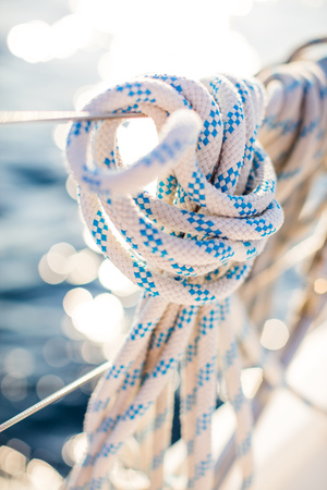 Detail of a mooring rope placed on sailing boat yacht desk. Leasure activities and extreme sport. Low depth of focus. Фото со стока