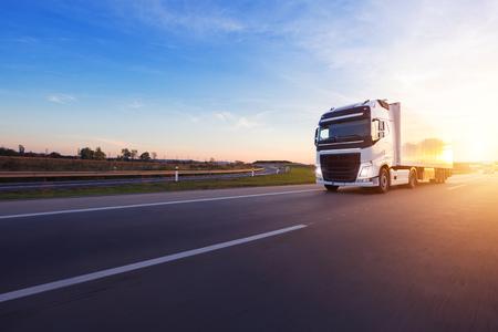 Camión europeo cargado en la autopista en la hermosa luz del atardecer. Transporte y carga por carretera. Foto de archivo