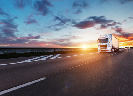 Loaded European truck on motorway in beautiful sunset light. On the road transportation and cargo. Archivio Fotografico