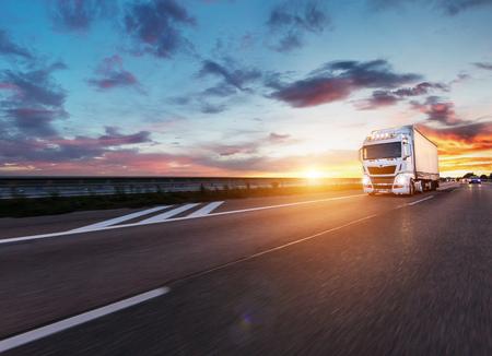 Geladen Europese vrachtwagen op snelweg in prachtig zonsonderganglicht. Vervoer over de weg en vracht.