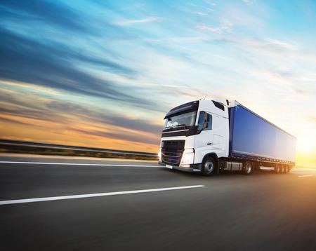Geladener europäischer LKW auf der Autobahn im schönen Sonnenuntergangslicht. Auf der Straße Transport und Fracht.
