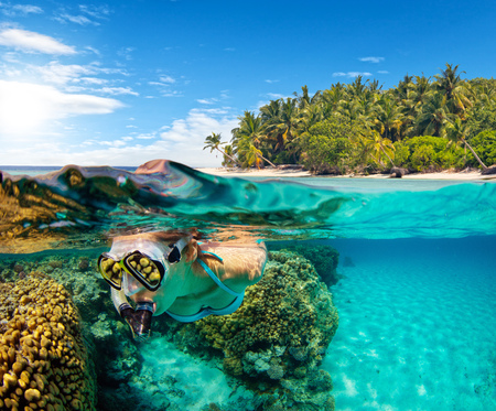 Under and above water surface view of woman snorkeling. Imagens