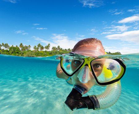 Under and above water surface view of woman snorkeling. Underwater fauna and flora, marine life and exotic island