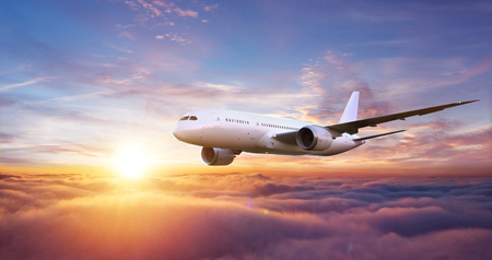 Huge two-storey passengers commercial airplane flying above clouds in sunset light.