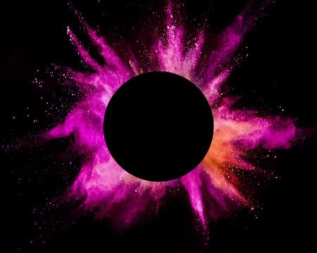 Explosion von farbigem Pulver mit leerem Kreis, auf schwarzem Hintergrund isoliert. Abstrakter farbiger Hintergrund
