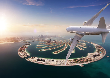 Commercial jet plane flying above Dubai city. Modern and fastest mode of transportation, business life and luxury style of life