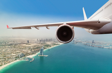 Detail of commercial jet plane flying above Dubai city. Modern and fastest mode of transportation, business life and luxury style of life
